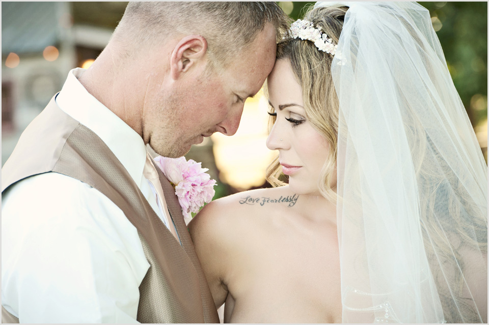 bride with a love fearlessly tattoo and groom