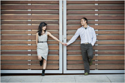 couple hold hands by doors in the Pearl district in Portland