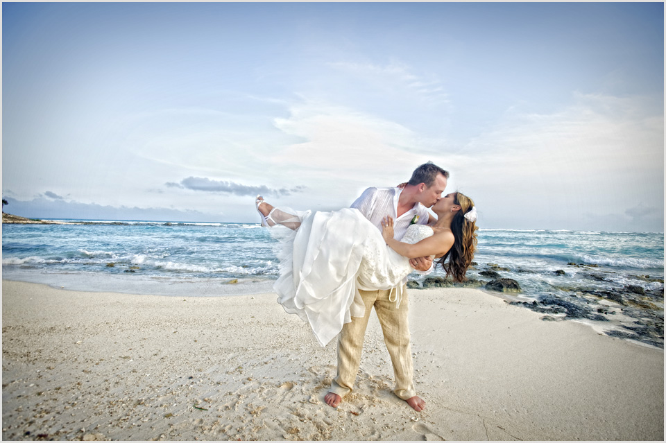 groom holds bride on the beach at Barcelo Maya Palace Mexico